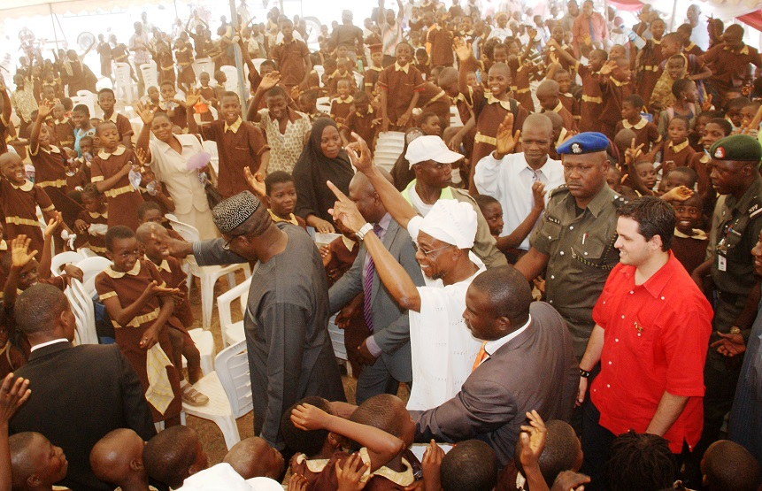 Governor State of Osun, Ogbeni Rauf Aregbesola; his Ekiti State counterpart, Dr Kayode Fayemi and Minister Counselor, Embassy of the Bolivarian Republic of Venezuela, Miguelangel Vecchia acknowledging cheers from the Pupils, at the Distribution of free Education Materials by the Venezuelan Ambassador in the Country to Students of Public Primary Schools in Osun, at the Distribution of free Education Materials by the Venezuelan Ambassador in the Country  to Students in Public Schools, commemorating 3rd years Anniversary of Aregbesola's Administration,  at Anthony Udofia Elementary School, Osogbo, State of Osun on Wednesday 27-11-2013