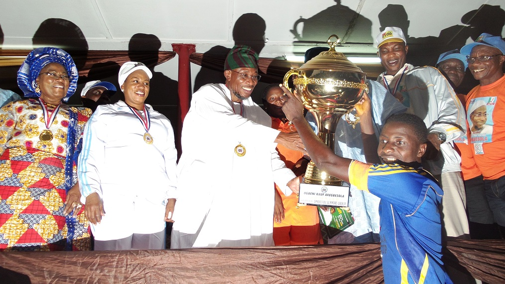 Governor, State of Osun, Ogbeni Rauf Aregbesola, presenting a victory cup of 1-0 to nothing to the captain of Orolu Football Club in the State, Master Oladele Afolabi, With them are, Deputy Governor, Mrs Titi Laoye-Tomori; wife of the Governor, Sherifat; Speaker of the House of Assembly, Hon. Najeem salami; Secretary to the State government, Alhaji Moshood Adeoti and others, during a football competition between Ede South Football Club and Orolu Foothball Club, tagged:  Governor Aregbesola's Cup, marking the 3rd year Anniversary celebration of Aregbesola's Administration, at Oba Olasore Oladele's Royal Park, Playing Ground, Iloko-Ijesa on Tuesday 26-11-2013