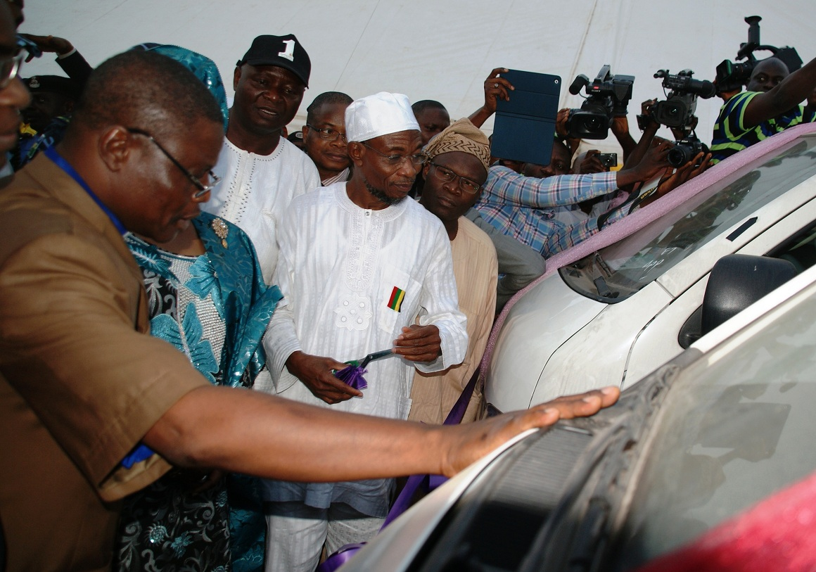 Chairman, Christian Association of Nigeria (CAN), State of Osun, Reverend Elijah Ogundiya (left), blessing the 70 Vehicles (18 sitter Toyota Commuter Bus) before distribution to members of the National Union of Road Transport Workers (NURTW) by the State Government. With him are Governor Rauf Aregbesola (in white cap); his deputy Mrs Titi Laoye-Tomori (2nd left); Commissioner for Commerce, Cooperative and Empowerment, Hon. Ismaila Jayeoba Alagbada (right) and others, during the commissioning/Distribution of the vehicles at the Governor's office, Abere, Osogbo, State of Osun on Monday 23-12-2013