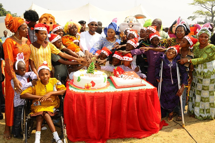 Governor State of Osun, Ogbeni Rauf Aregbesola and his wife, Sherifat helping the Childrens in cutting the cake, marking  the Xmas/ End of the Year Party organised for the State Children by the Wife of the State Governor in collaboration with the  Ministry of Women and Children Affairs, at Government House Lawn, Osogbo, State of Osun on Monday 23-12-2013 With them are, Commissioner for Women and Children Affairs, Mrs Mofolake Adegboyega (left); Special Adviser to the Governor on Women and Children Affairs, Barrister Funmilayo Eso-Williams (2nd right) and others on Monday 23-12-2013