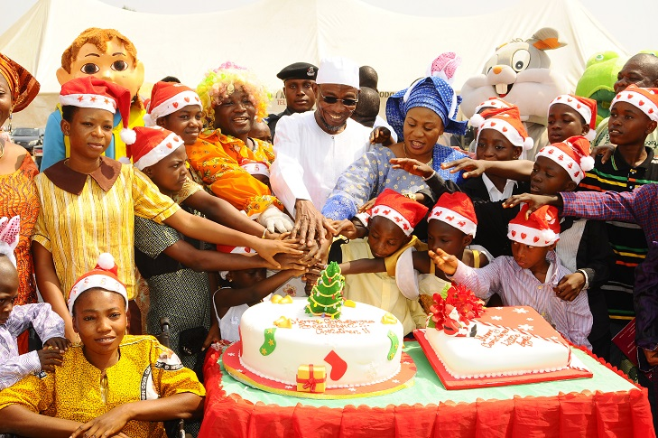 Governor State of Osun, Ogbeni Rauf Aregbesola and his wife, Sherifat helping the Childrens in cutting the cake,  during the Xmas/ End of the Year Party organised for the State Children by the Wife of the State Governor in collaboration with the  Ministry of Women and Children Affairs, at Government House Lawn, Osogbo, State of Osun on Monday 23-12-2013