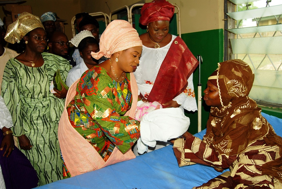 Wife of the Governor, State of Osun, Alhaja Sherifat Aregbesola (2nd left); Commissioner for Health, Mrs Temitope Ilori (2nd right); Permanent Secretary, Hospitals Management Board, Pharmacist Omolara Ajayi (left); Mother of the Baby (right) and others, during her donation of gifts to the First Baby of the Year born at 12.01am, at Primary Health Care Centre, Iwo, State of Osun on Wednesday 01-01-2014