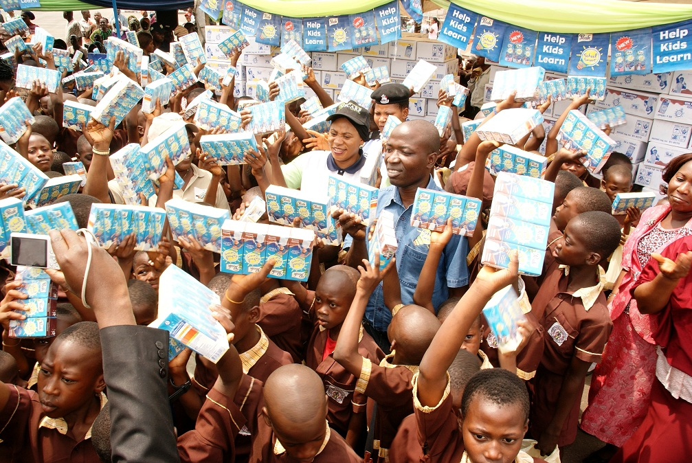 Wife of the Governor, State of Osun, Mrs Sherifat Aregbesola; Managing Director, Peak School Smart, Mr Ezekiel Salami and the Pupils in Public Elementary Schools in the State displaying their Sheri Care Foundation (SCARF) Milk of Knowledge, during the Distribution at Nelson Mandela Freedom Park, Osogbo, State of Osun on Thursday 20-02-2014
