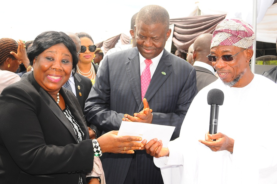 Governor State of Osun, Ogbeni Rauf Aregbesola (right) presenting a Smart ID Card to Chief Judge State of Osun, Justice Adepele Ojo (left), during the launch of the State Civil Servant Smart ID Card and Biometric Automation of 'I am alive' at Office of the Governor Parking lot, State Secretariat, Osogbo, State of Osun on Tuesday 29-04-2014. With them is, General Managing Director, Charms Plc, Sir Demola Aladekomo (middle).