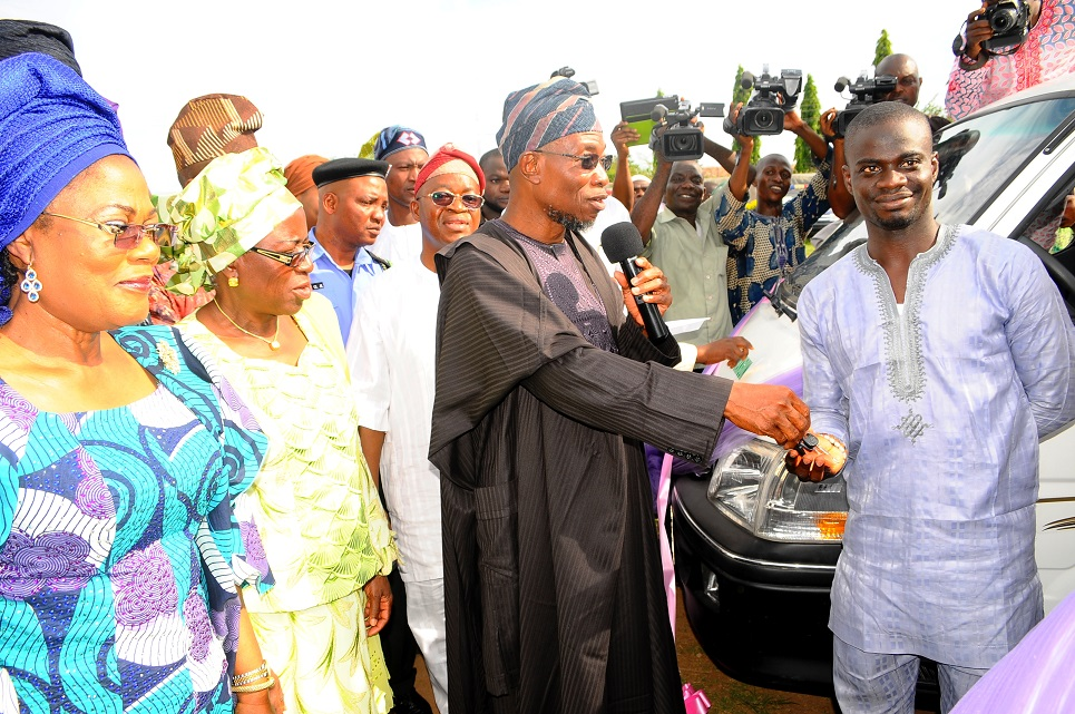 Governor State of Osun, Ogbeni Rauf Aregbesola (2nd right) Presenting an 18-seater Bus key to President, Student Union Government (SUG), Osun State College of Education, Ila-Orangun, Comrade Saheed Badmus (right), during the Presentation of four 18-seater Buses to the SUG of the State-Owned Tertiary Institutions at Government House Lawn, Osogbo, State of Osun on Friday 02-05-2014. With them are, Deputy Governor, Mrs Titi Laoye-Tomori (left); Special Adviser to the Governor on Tertiary Institutions, Alhaja Mulikat Bello (2nd left) and others.