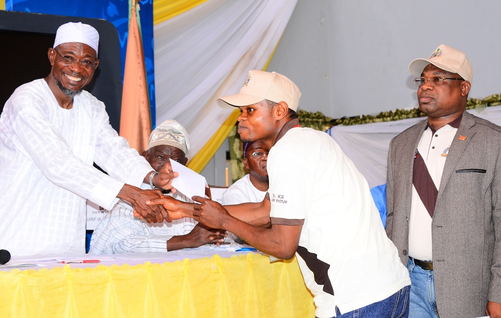 Governor State of Osun, Ogbeni Rauf Aregbesola (left) Presenting Stipends to one of the Trainees, Mr Popoola Morufu (2nd right); Managing Director, Osun State Investment Company Limited (OSICOL), Alhaji Bola Oyebamiji (right) and others, during the Sent-forth Ceremony for 31 Indigenes of Osun on a Two-month Mechatronics in-plant and end-user training in Germany at, Government House Banquet Hall, Osogbo, State of Osun on Monday 02-06-2014