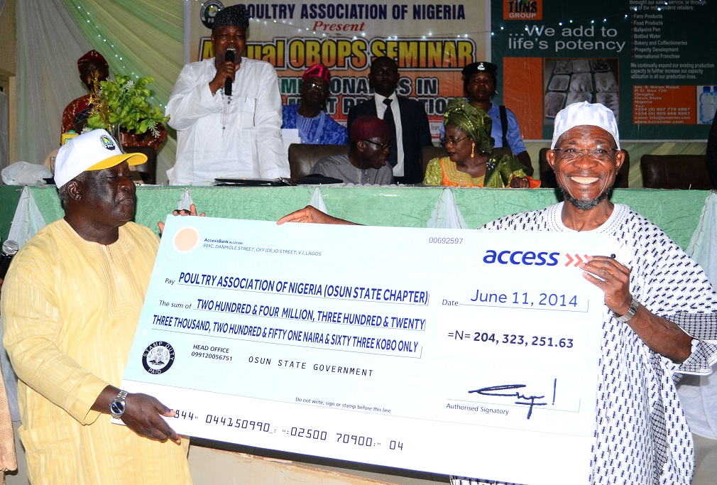 Governor State of Osun, Ogbeni Rauf Aregbesola (right) Presenting a Cheque to Chairman, Poultry Association of Nigeria (PAN), Osun Chapter, Chief Oluyemi Olukiran, during an Annual Seminar for Osun Broiler Out-Growers' Production Scheme (OBOPS) and presentation of cheque to the association by the Governor at Royal Spring Holiday Inn, Osogbo, State of Osun on Thursday 12-06-2014