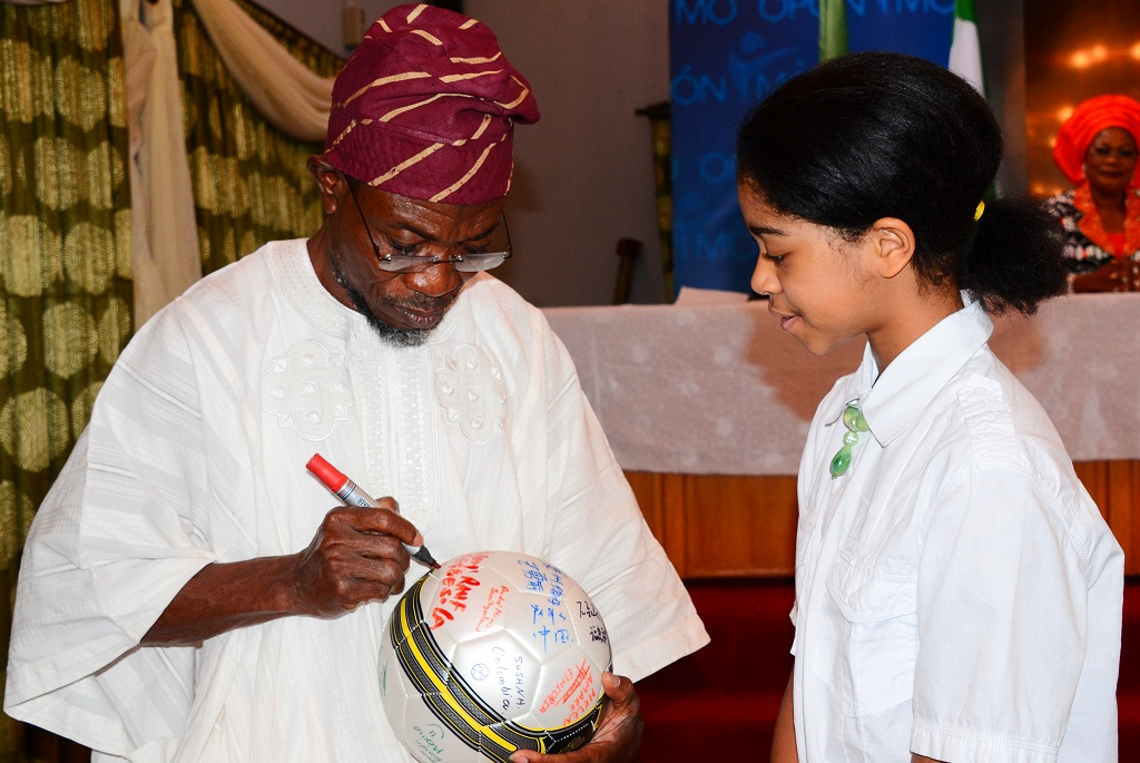 Governor State of Osun, Ogbeni Rauf Aregbesola signing a Football to make Case for Girls Education after receiving an Award as the Most Innovative Governor Supporting Education in Nigeria at Government House Banquet Hall, Osogbo, State of Osun. With him is, Initiator, Dream up; Speak up & Stand up Project/International Ambassador on Child Education Development, Miss  Zuriel Oduwole on Wednesday 02-07-2014