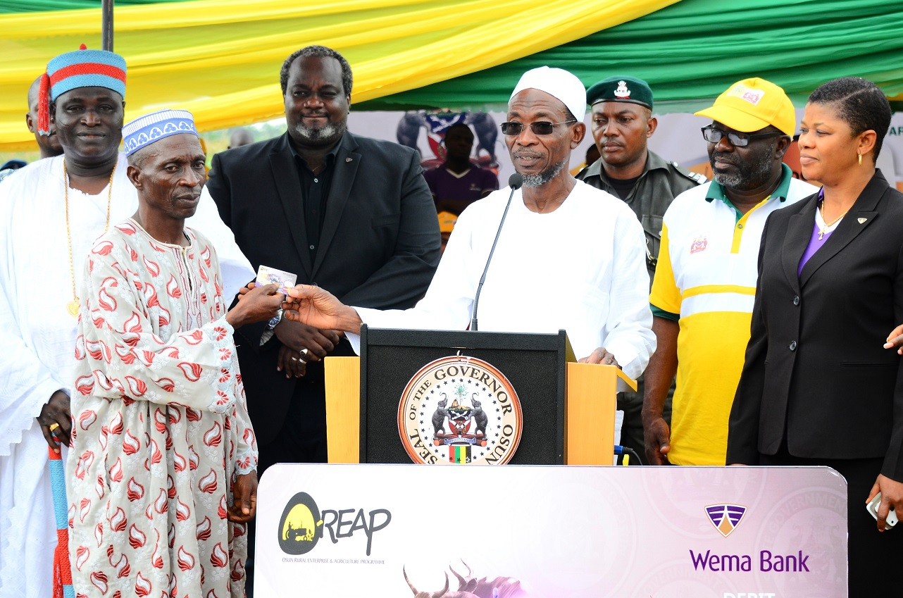 Governor State of Osun, Ogbeni Rauf Aregbesola (3rd right) giving a Debit Card to a Farmer, Mr Sikiru Omoniyi (2nd left), during the OfficialLaunching of the Framers Input and Credit Support Programme, at the Central Distribution Centre, Ede. With them are, Timi of Edeland, Oba Munirudeen Lawal (left); Coordinator, Osun Rural Enterprise and Agricultural Programme (OREAP), Dr Charles Akinola (2nd right); Zonal Manager, Wema Bank Plc, Osun Zone, Mrs Bisi Williams (right); Head, Card Business and Services, Wema Bank Plc Lagos, Mr Demola Bolodeoku (3rd left)