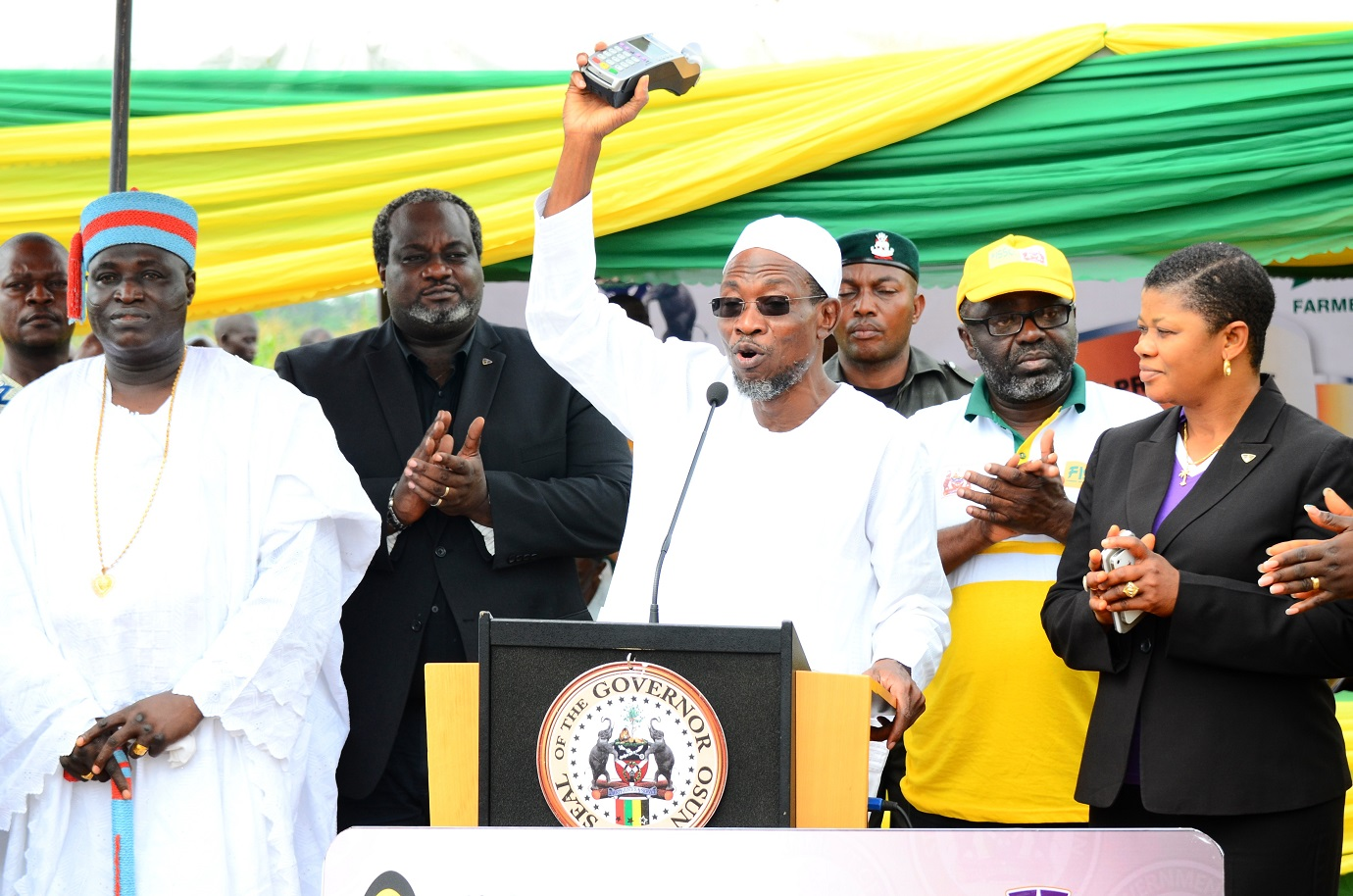 Governor State of Osun, Ogbeni Rauf Aregbesola (centre) displaying the Point of Sales (POS) Terminal to be used by Osun Farmers for Farming Input Purchase, during the Official Launching of the Framers Input and Credit Support Programme, at the Central Distribution Centre, Ede. With him are, Timi of Edeland, Oba Munirudeen Lawal (left); Coordinator, Osun Rural Enterprise and Agricultural Programme (OREAP), Dr Charles Akinola (2nd right); Zonal Manager, Wema Bank Plc, Osun Zone, Mrs Bisi Williams (right) and Head, Card Business and Services, Wema Bank Plc Lagos, Mr Demola Bolodeoku (2nd left)