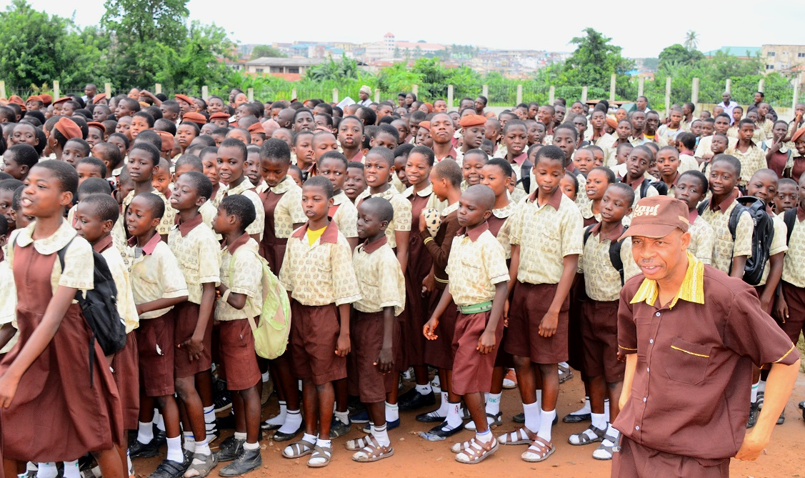Nollywood Comic Actor, Mr Hafiz Oyetoro also known as Saka (right, with face cap) on the Assembly Ground with Students of Salvation Army Middle School, during his Visit to the School at Alekuwodo, Osogbo, State of Osun on Thursday 03-07-2014