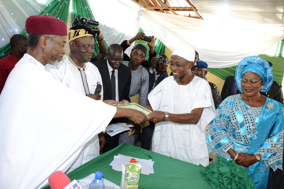 National Commissioner, Independent National Electoral Commission (INEC), Ambassador Muhammed Wali (left); presenting Certificate of Return to the Governor of the State of Osun, Ogbeni Rauf Aregbesola. With them are, Deputy Governor, Mrs Titi Laoye-Tomori; Secretary of the Commission, Mr .Oladipo Oladapo; Acting Director, Legal, Mr Ibrahim Bawa (3rd left) and others, at the INEC office, Osogbo, State of Osun on Tuesday 12-08-2014