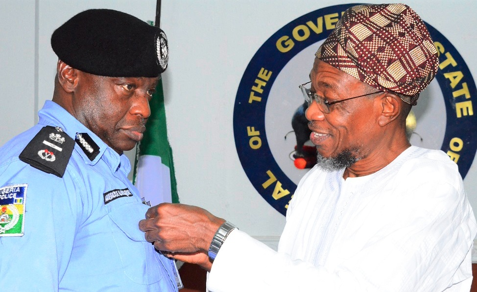 Governor State of Osun, Ogbeni Rauf Aregbesola decorating the Assistant Inspector General of Police (AIG) Zone 11, Ambrose Aisabor, during a courtesy visit to the Governor at Government House, Osogbo on 21/10/2014.