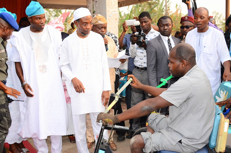 Ogbeni Rauf Aregbesola presenting wheelchairs the physically challenged persons in Boripe LGA