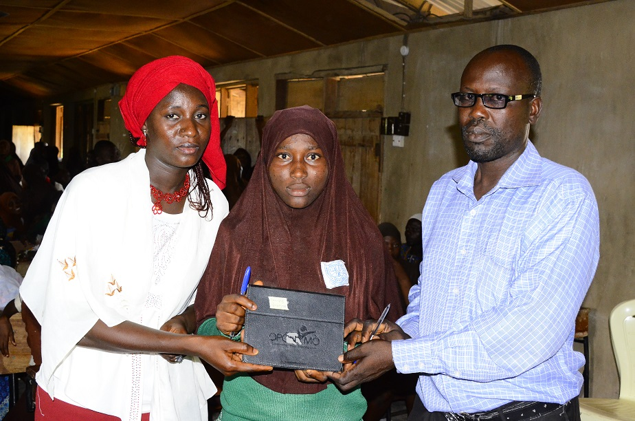 Vice Principal Agbonran Science High School, Ede, Mr Adesiyan John (right) handing over 'Opon Imo' - Tablet of Knowledge to one of his student, Abdullahi Fatimoh (middle) with them is her mother, Mrs Rukayat, during the free distribution of the tablet at the school hall
