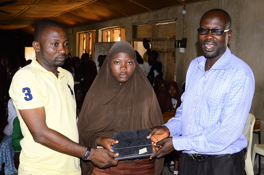 Vice Principal Agbonran Science High School, Ede, Mr Adesiyan John (right) handing over 'Opon Imo' - Tablet of Knowledge to one of his student, Babatunde Morufat (middle). With them is her father, Mr Alade, during the free distribution of the tablet at the school hall